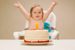 Baby girl sitting in high chair with arms outstretched celebrating first birthday with cake